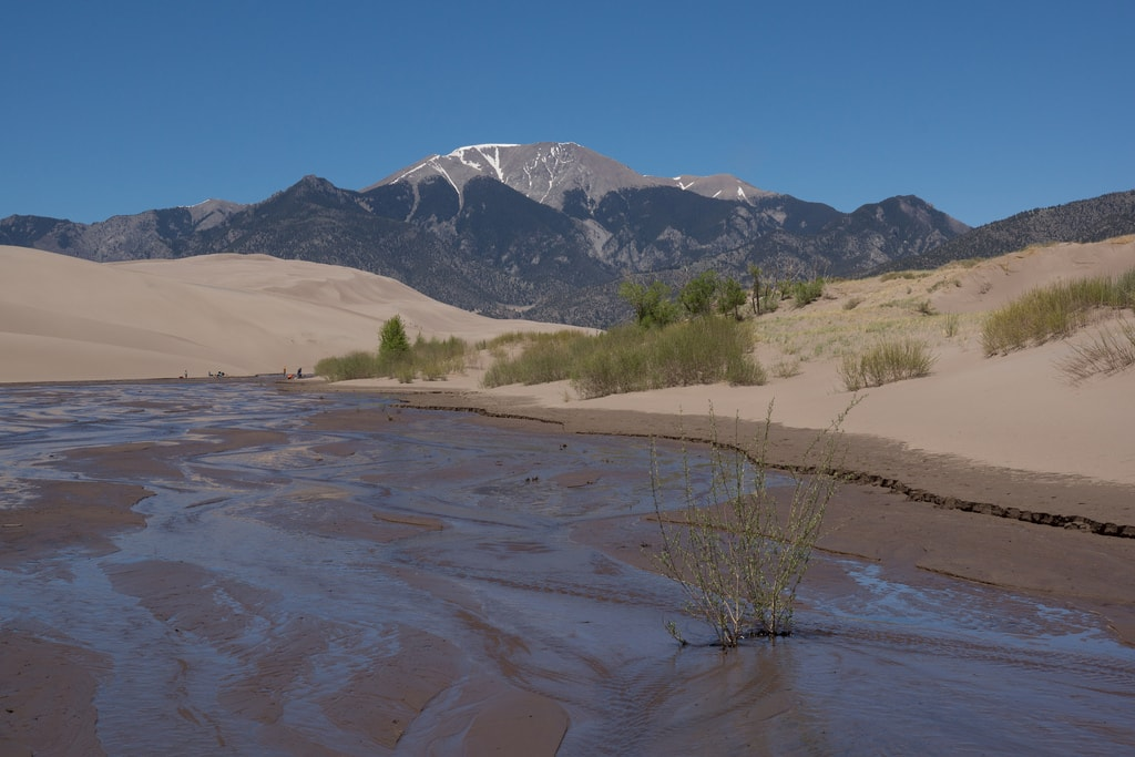 Medano Creek at Great Sand Dunes National Park in Colorado - Build a sandcastle, sun-bathe, and if the water is high enough, skimboard or take a quick dip.