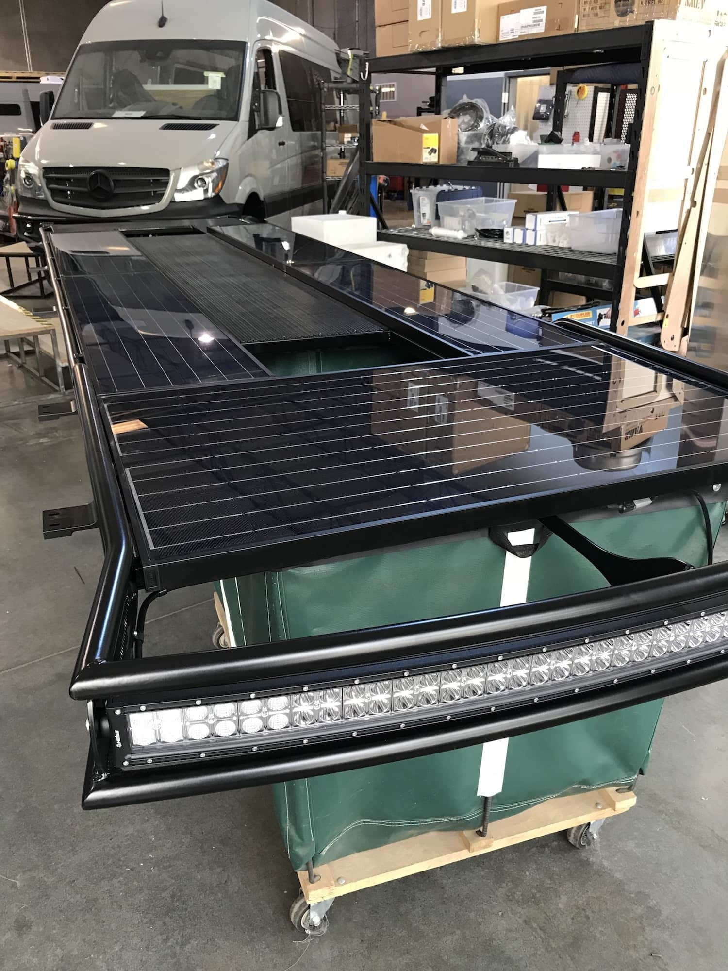 Outside Van Sprinter roof rack with Zamp solar panels and light bar