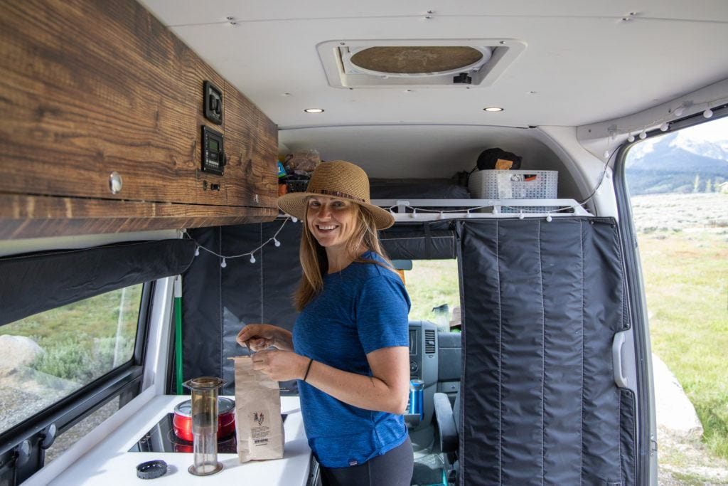 A hat helps cover up greasy hair in between showers while traveling in a van.