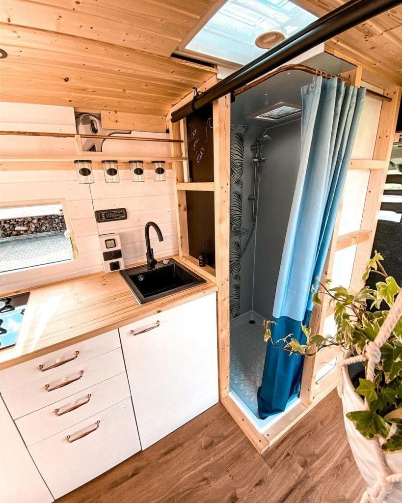 Camper van bathroom setup with indoor shower and portable toilet by @makai.the.van