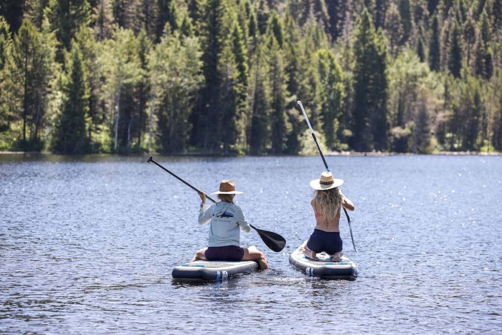 Two girls kneeling while paddleboarding on a lake // Want to try stand up paddleboarding this summer? Learn the basics of SUP with our paddle boarding for beginners guide including tips and gear!