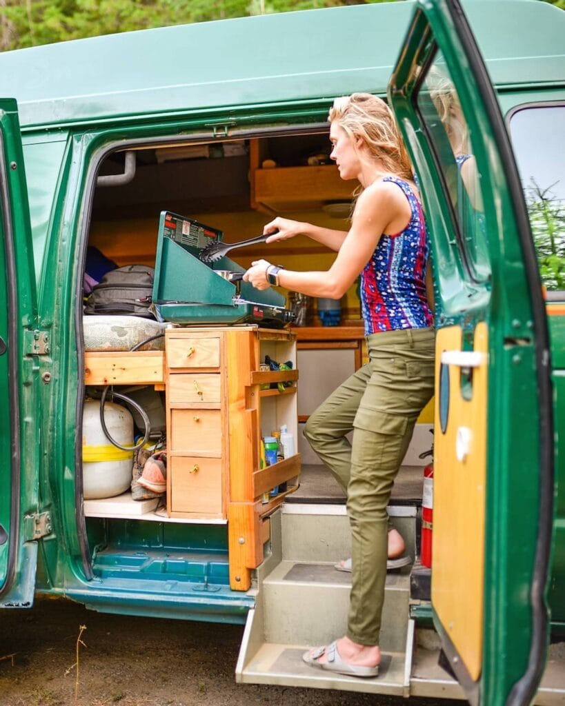 Woman cooking on a propane stove in a budget DIY green Ford Econoline camper van