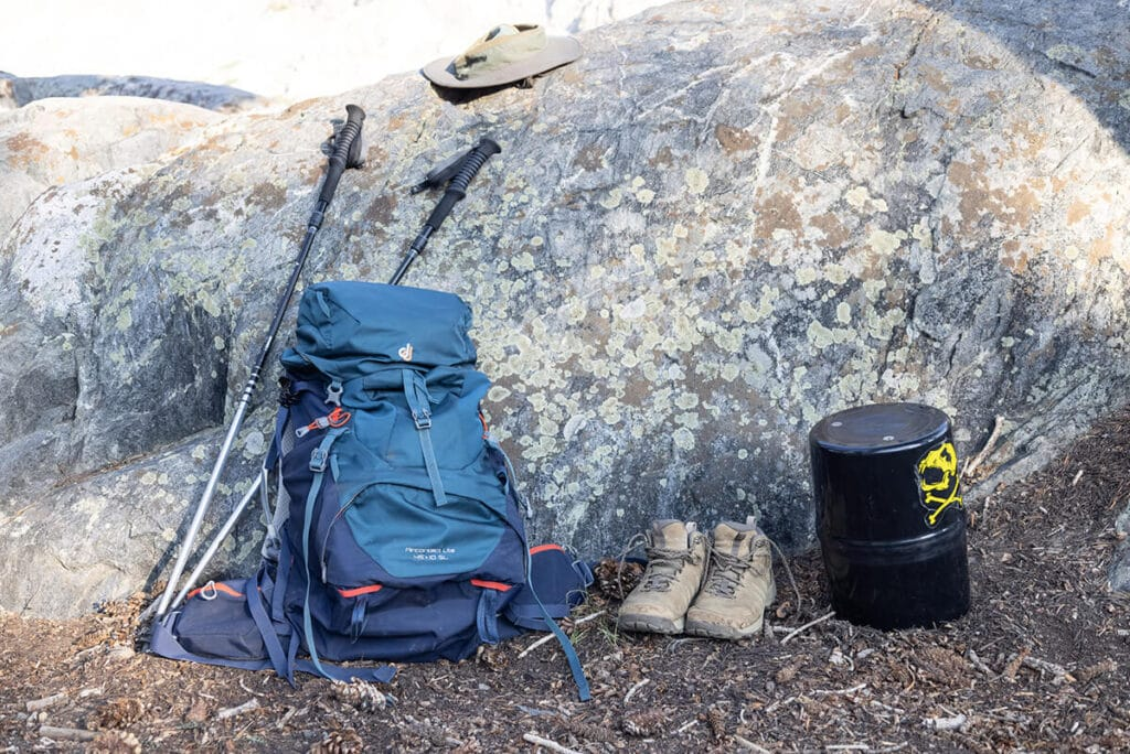 Backpacking gear including a backpacking pack, trekking poles, hat, hiking boots, and a bear canister